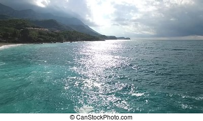 Azure beach with rocky mountains and clear water. Footage. Aerial