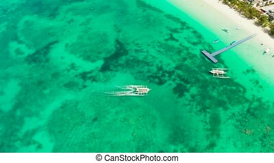 Lagoon with turquoise water and speed boat, top view. Seascape with beach on tropical island. Summer and travel vacation concept. Boracay Island, Philippines