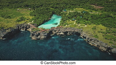 Azure lake on green rock coast at sea bay in aerial view. ...