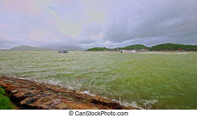 Azure Sea Waves Break at Rocky Bank against Cloudy Sky -...