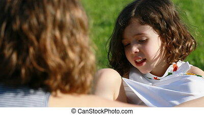 B girl talking to A girl outdoors