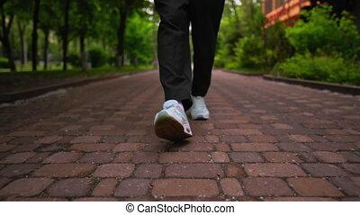 b roll male feet walks in town summer season - close up legs...