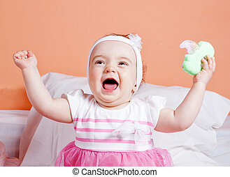 Babe girl playing laughing toy. One year.