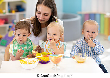 Babies having lunch in kindergarten. Kids eat healthy food in creche. Carer with children sitting at dinner table in canteen