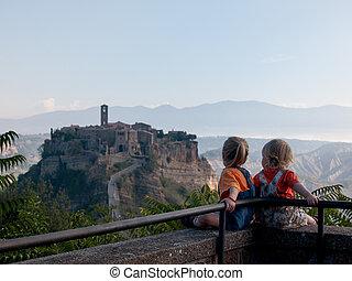Babies looking at Civita di Bagnoregio. Italy