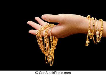 babska ręka, z, dużo, różny, złota biżuteria, na, czarne tło