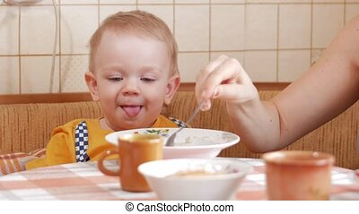 Baby 2 years old eats porridge with a spoon. Mom sits next to the boy. home furnishings