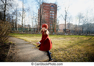 Baby 3 years with long hair. In a red beret and coat spinning in the street , in the rays of the sun.