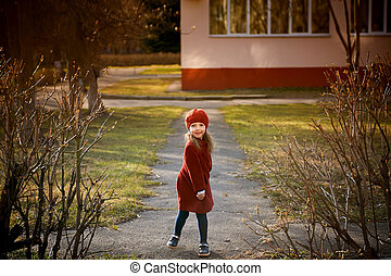Baby 3 years with long hair. In a red beret and coat spinning in the street , in the rays of the sun. The state of happiness.Childhood