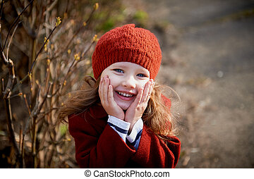 Baby 3 years with long hair. In a red beret and coat stands on the street in the sunshine, holding the handle of the face and smiles