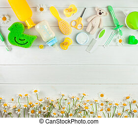 Baby accessories for bath near chamomile flowers over white ...