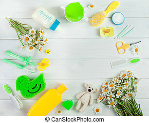 Baby accessories, toys and chamomile flowers in round shape ...