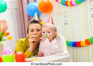 Baby and mother blowing into party horn