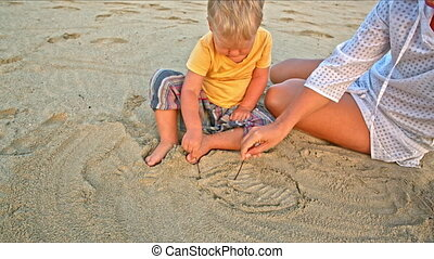 Baby and mother draw in sand on bea