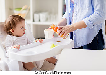 baby and mother pouring juice to cup at home