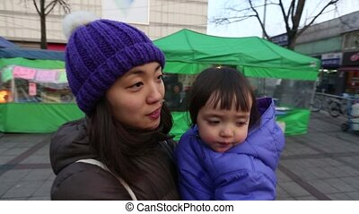 Baby and Mother Walking in City - Glide cam shot of a Korean...