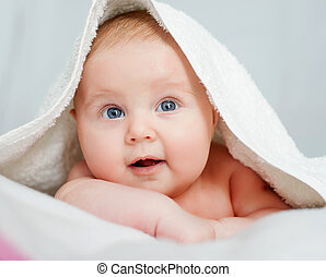 baby and the towel - A young baby on a white bed with a...