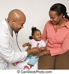 Baby at doctor. - African-American male doctor examining...