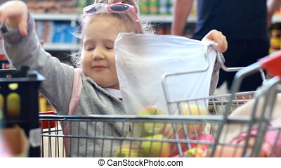 Baby at the grocery store buys fruit. Child girl siting in...