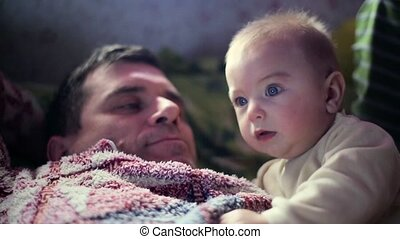 Baby Attentively watch TV. Dark backgroung, With Dad Father