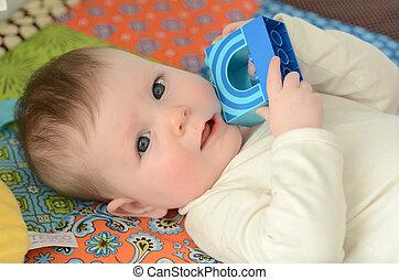 Baby awake  - Portrait of a baby awake on a baby floor mat.