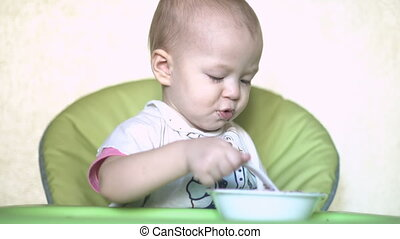Baby bangs spoon on plate.