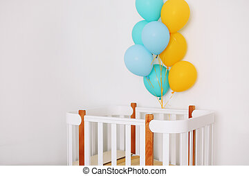 Baby bedroom interior. Minimalistic baby room interior. Festive balloons in front of baby bed. Baby birthday celebration concept.
