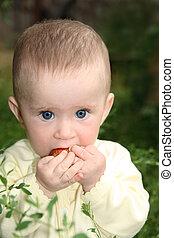 baby biting apple in grass