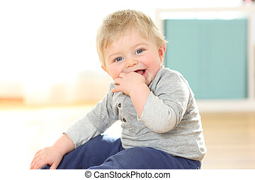 Baby biting fingers looking at camera on the floor