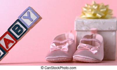 Baby blocks toppling over in front of booties and gift box...