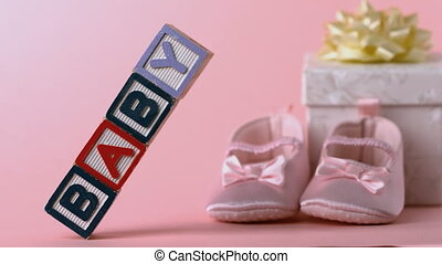Baby blocks toppling over with booties and gift box in...