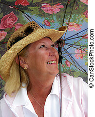 Baby Boomer - Woman with hat under a floral umbrella.
