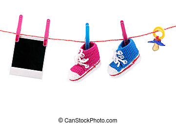 Baby bootees, photo and dummy on the clothesline on a white ...