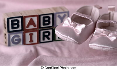 Baby booties falling on pink blanke