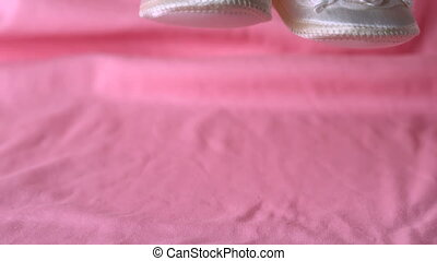 Baby booties falling on pink blanket in slow motion
