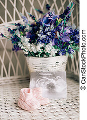 Baby booties on a wicker chair and a bouquet of lavender on a ba