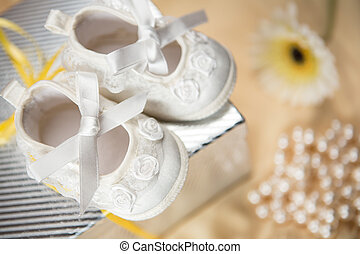 Baby booties on gift box on a yellow blanket with pearl...