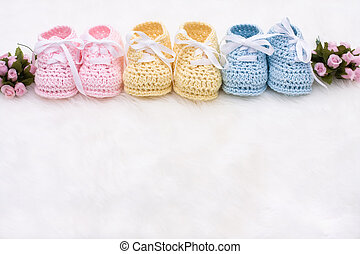 Baby Booties - Three pairs of baby booties on a white...