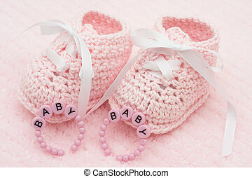 Baby Booties - Baby booties with bracelets on a pink...
