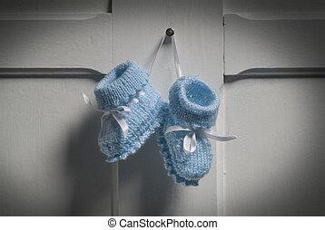 Baby Booties - Blue Baby Booties hanging on white door