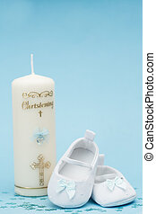 Baby booties with blue ribbon and christening candle on blue...