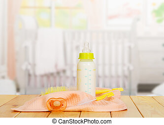 Baby bottle with milk, pacifier and towel on  background  kitchen.