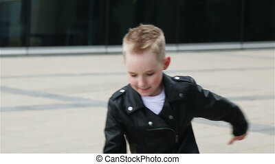 baby boy 7 - 8 years in a black leather jacket dancing in...