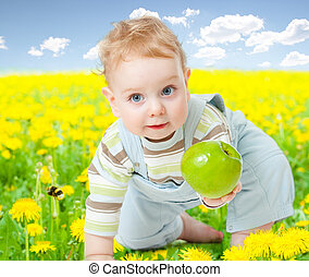 Baby boy among dandelion with healthy food apple in his hand