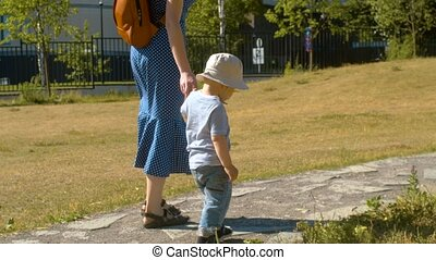 Baby boy and his mom walking in the park
