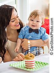 Baby Boy And Mother With Birthday Cake On Table