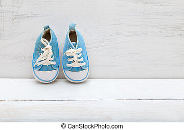 baby boy blue sneakers on white wooden background