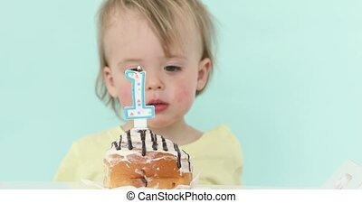 Baby boy celebrating first birthday blowing candle