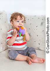 Baby boy chewing on toy