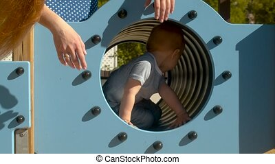 Baby boy crawls in the tube in the park on the playground